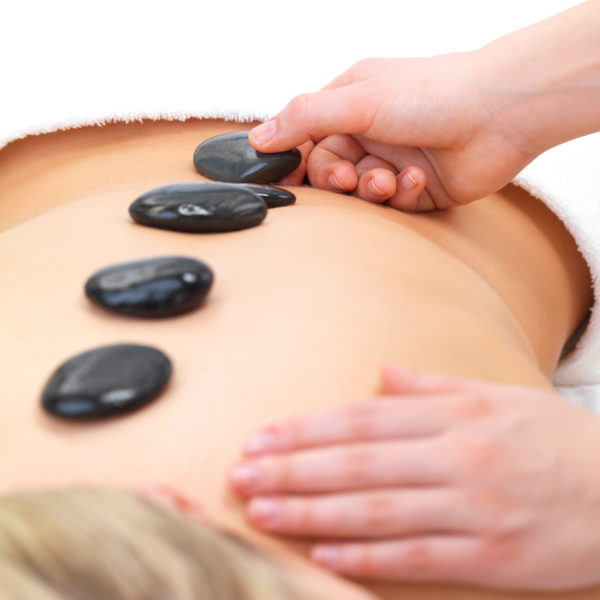 Hot stones on back of a young female - Portrait of a beautiful young girl at the day spa with black stones on her bare back